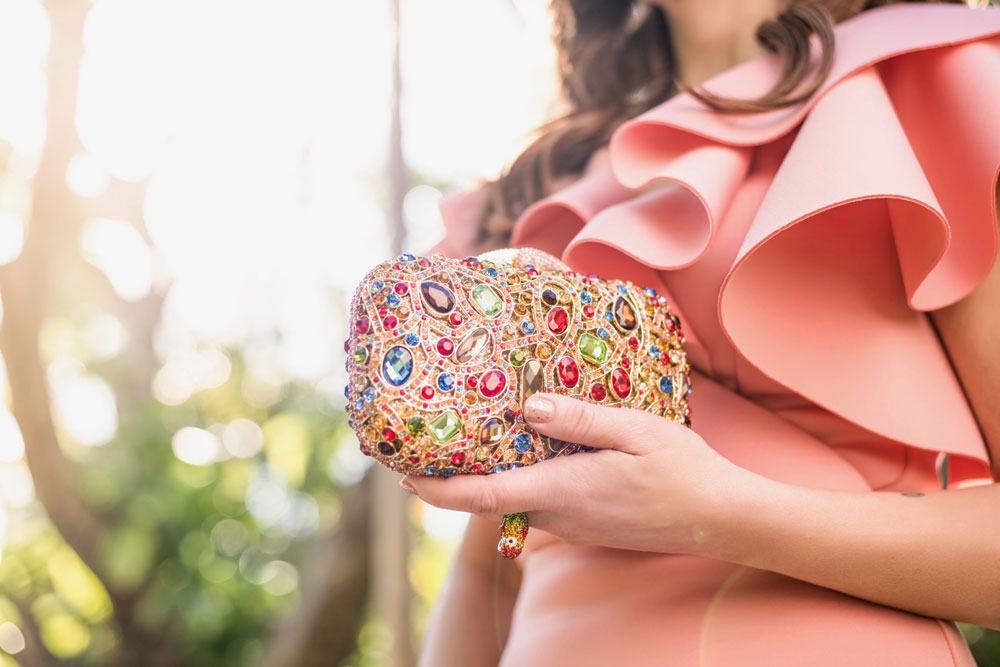 A Christmas Clutch. Shireen Sandoval fashion blog, Miami FL. Wearing a peach ruffle dress by Vchic Boutique and holding a glamorous evening clutch by The Limelight Collection. Bedazzled purses, bags and clutches for the holidays. Also featured on Deco Drive Television and photographed by James Woodley